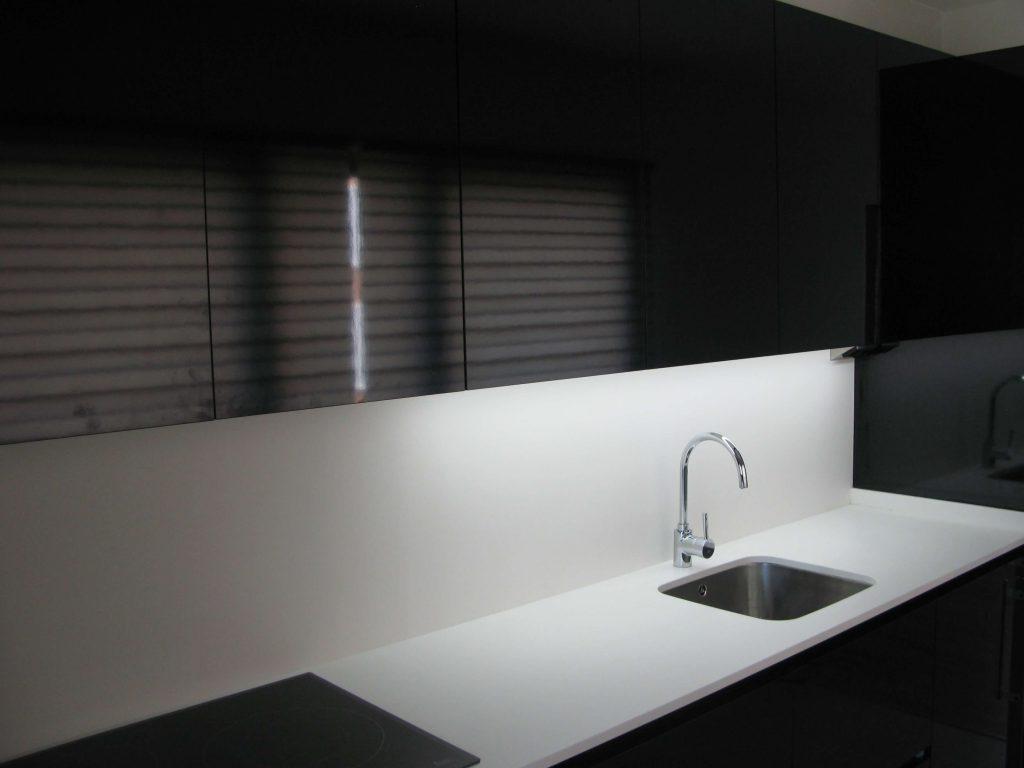 Cocina alargada en negro Duropal brillo canteado en láser. Detalle fregadero integrado