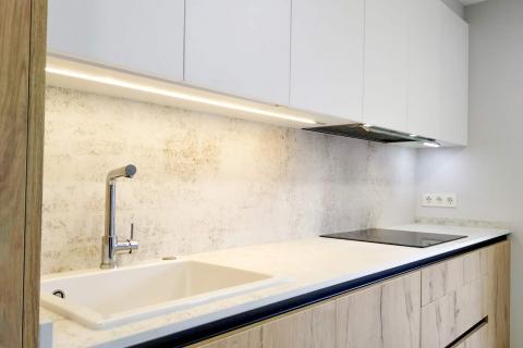 Cocina moderna en color blanco y madera: Detalle de iluminación LED inferior del mueble alto