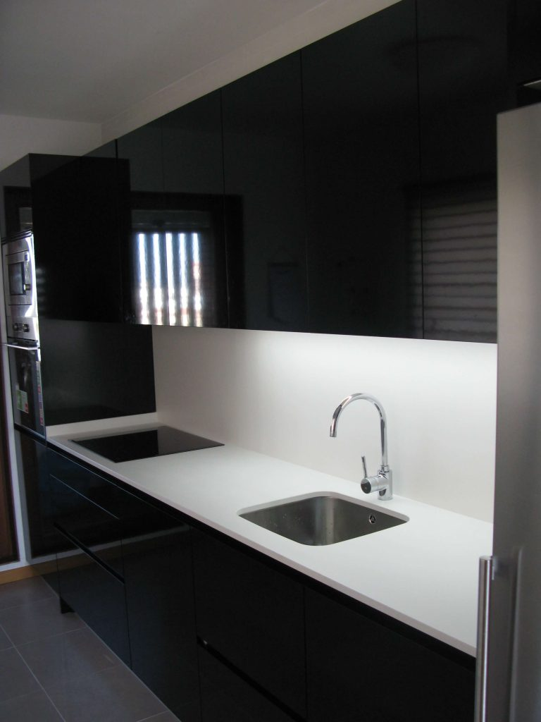 Cocina alargada cocinas vitoria tierra home design for Encimera negra brillo