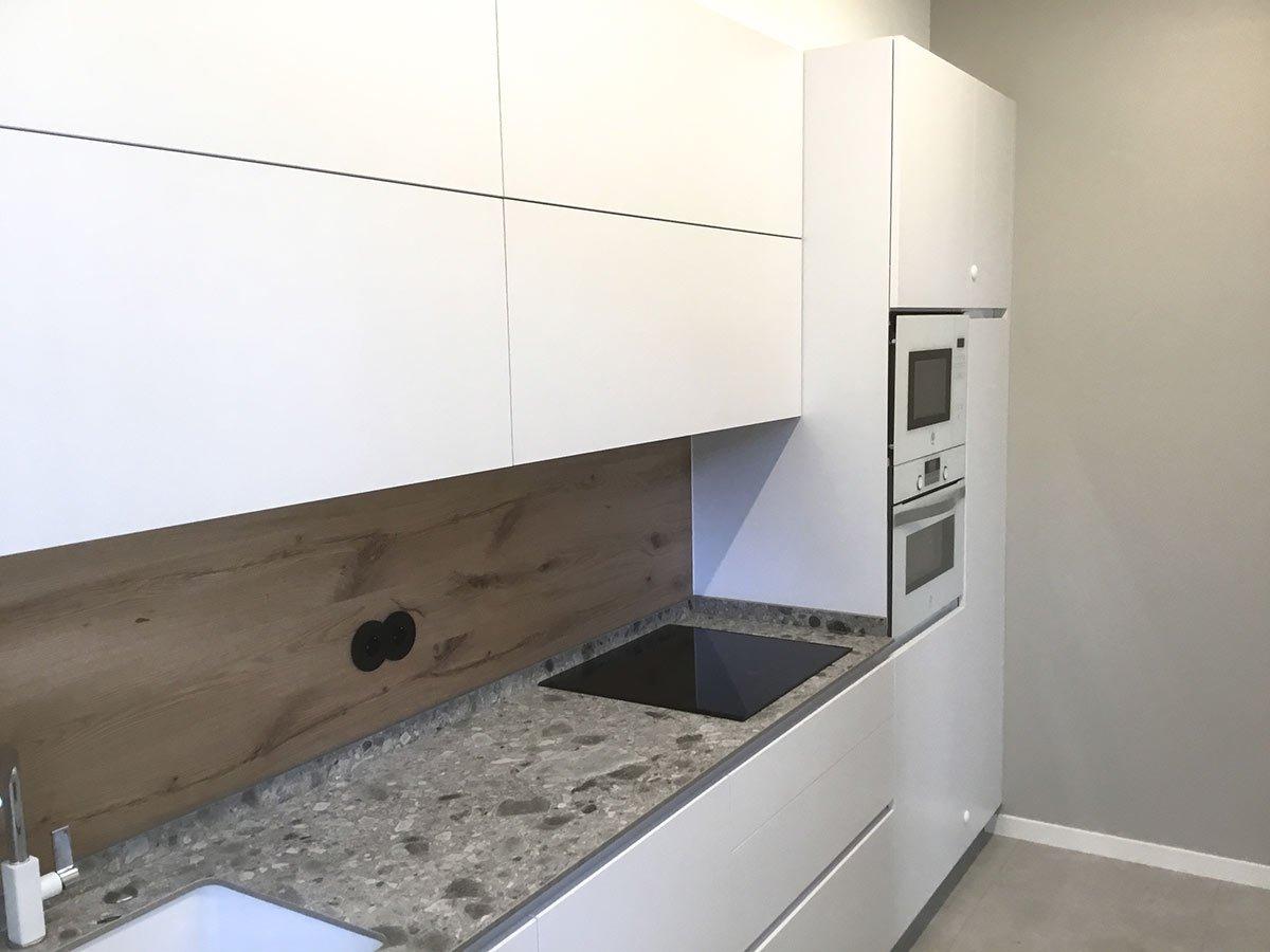 Cocina blanca y encimera de granito con frigorífico Side by Side